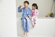 Brother and sister sitting on edge of bath with toothbrushes - ISF17997