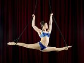 Studio shot of female aerialist performing splits on ropes - ISF18018