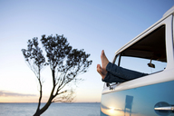 Feet out of camper van window at dusk - ISF18132