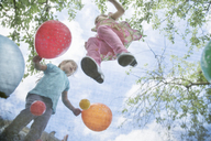Young girls jumping on garden trampoline with balloons - ISF18249