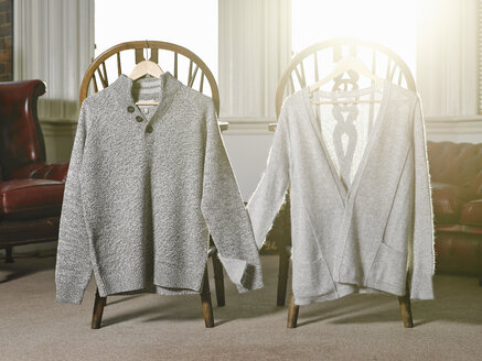 Two sweaters on coat hangers holding hands - ISF18327