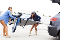 Female friends pulling cover from surfboard - ISF18351