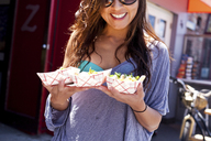 Woman with takeaway food, Hermosa Beach, California, USA - ISF18360