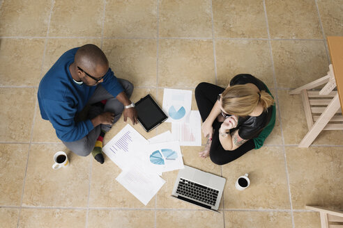 Young business partners sitting on floor in design office - ISF18403