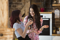 Happy female friends at home drinking white wine - AWF00148