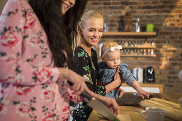 Female friends with baby girl preparing dinner together - AWF00154