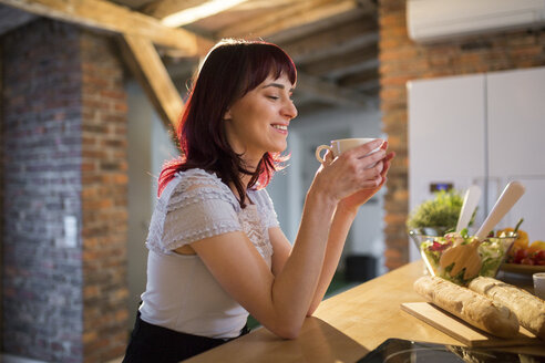 Smiling woman drinking cup of coffee in kitchen at home - AWF00157