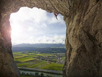 Austria, Innsbruck, Martinswand, man climbing in grotto - CVF01003
