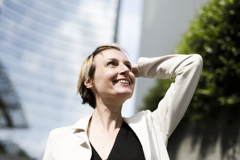 Portrait of smiling businesswoman looking up - GIOF04012