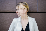Blond businesswoman leaning against wall, dopple exposure - GIOF04027