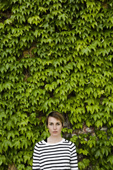 Portrait of woman in front of facade greenery - GIOF04039