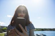 Italy, Lake Garda, portrait of young woman wearing sunglasses using smartphone - GIOF04047