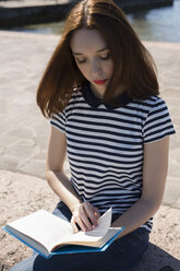 Portrait of young woman sitting on wall reading a book - GIOF04050