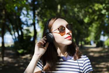 Portrait of young woman wearing sunglasses listening music with headphones - GIOF04053
