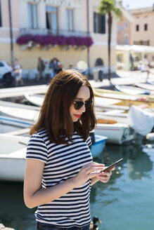 Italy, Bardolino, Lake Garda, young woman using cell phone - GIOF04056
