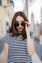 Italy, Bardolino, portrait of young woman with red lips and sunglasses - GIOF04059