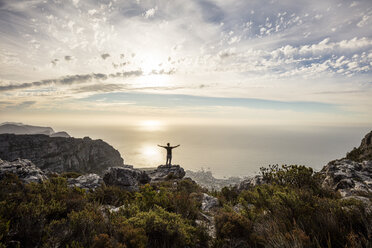 South Africa, Cape Town, Table Mountain, man standing on a rock at sunset - DAWF00684