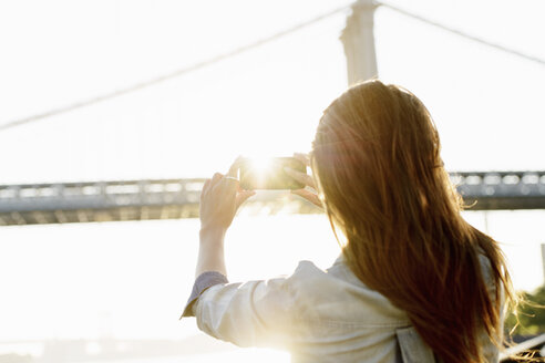 Young woman photographing Manhattan Bridge, Brooklyn, USA - ISF18596