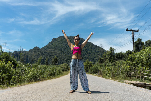 Laos, Vang Vieng, woman standing on country road with raised arms - AFVF01152