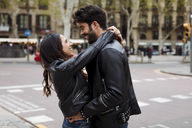 Spain, Barcelona, happy young couple hugging on the street - MAUF01540