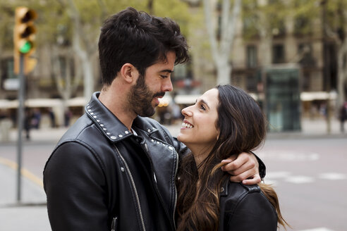 Spain, Barcelona, happy young couple hugging on the street - MAUF01543