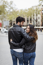 Spain, Barcelona, young couple embracing and walking in the city - MAUF01546