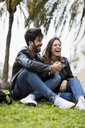 Spain, Barcelona, laughing young couple sitting on meadow - MAUF01549