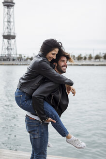 Spain, Barcelona, happy young couple having fun at the coast - MAUF01552