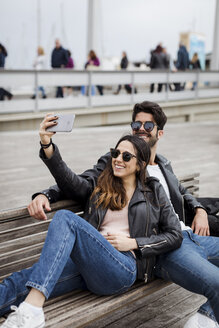 Spain, Barcelona, happy young couple resting on a bench taking a selfie - MAUF01555