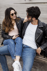Happy young couple with cell phone resting on a bench - MAUF01558