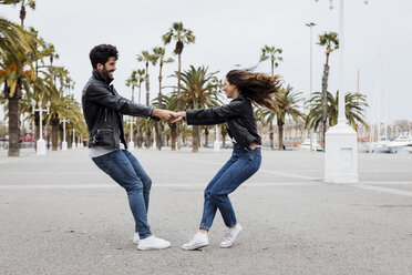 Spain, Barcelona, happy young couple having fun on promenade with palms - MAUF01561