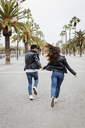 Spain, Barcelona, happy young couple running on promenade with palms - MAUF01564