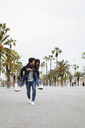 Spain, Barcelona, young man carrying happy girlfriend on promenade with palms - MAUF01567