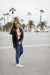 Spain, Barcelona, happy young woman standing on promenade with palms - MAUF01570