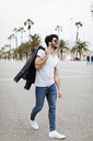 Spain, Barcelona, young man walking on promenade with palms - MAUF01576