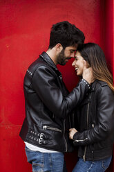 Affectionate happy young couple standing at red door - MAUF01579