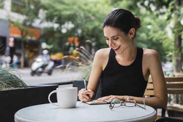 Young woman sitting in coffee shop, brainstorming, writing notes in notebook - KKAF01260