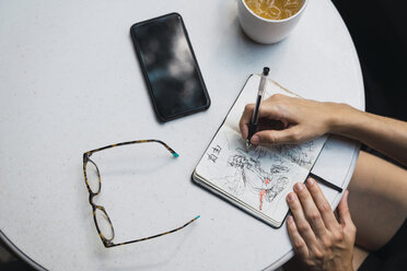 Hands of woman sketching in notebook, glasses, tea and smartphone on table - KKAF01263