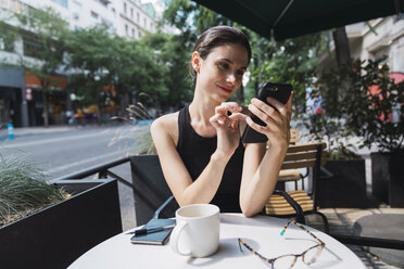 Young woman sitting in cofee shop, using smartphone - KKAF01266