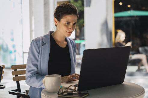 Young businesswoman sitting in coffee shop, using laptop - KKAF01269