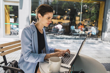 Young businesswoman sitting in coffee shop, using laptop - KKAF01272
