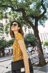 Beautiful woman wearing yellow dress with polka dots, walking in the city - KKAF01281