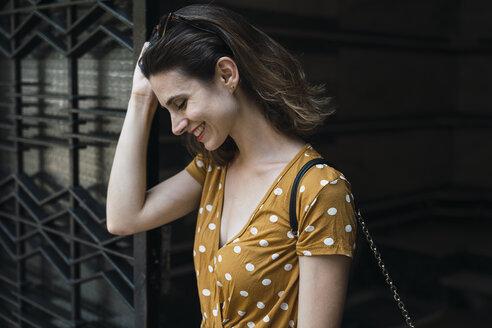 Laughing woman wearing yellow dress with polka dots - KKAF01287