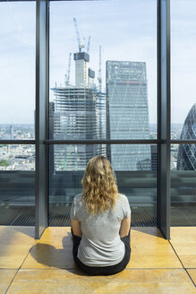 UK, London, back view of young woman looking at skyscrapers of financial district - AFV01161