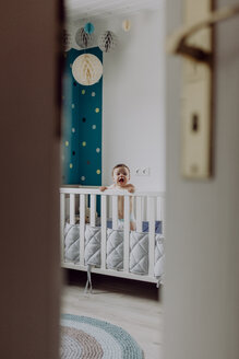 Baby boy standing in his cot, laughing - JLOF00141