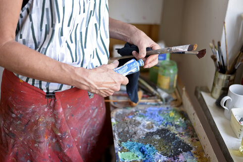 Female painter in her atelier, paint tube and paintbrushes - BFRF01882