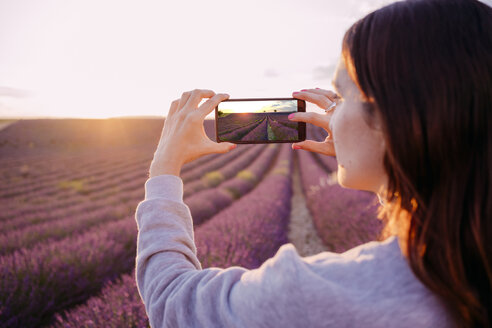 France, Valensole, woman taking photo of lavender field at sunset - GEMF02218