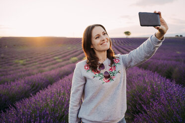 France, Valensole, portrait of smiling woman taking selfie in front of lavender field at sunset - GEMF02221