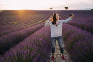 France, Valensole, smiling woman taking selfie at lavender field by sunset - GEMF02224