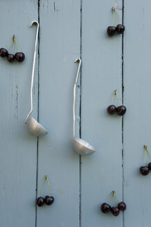 Cherries and two laddles hanging on wooden wall - GISF00341